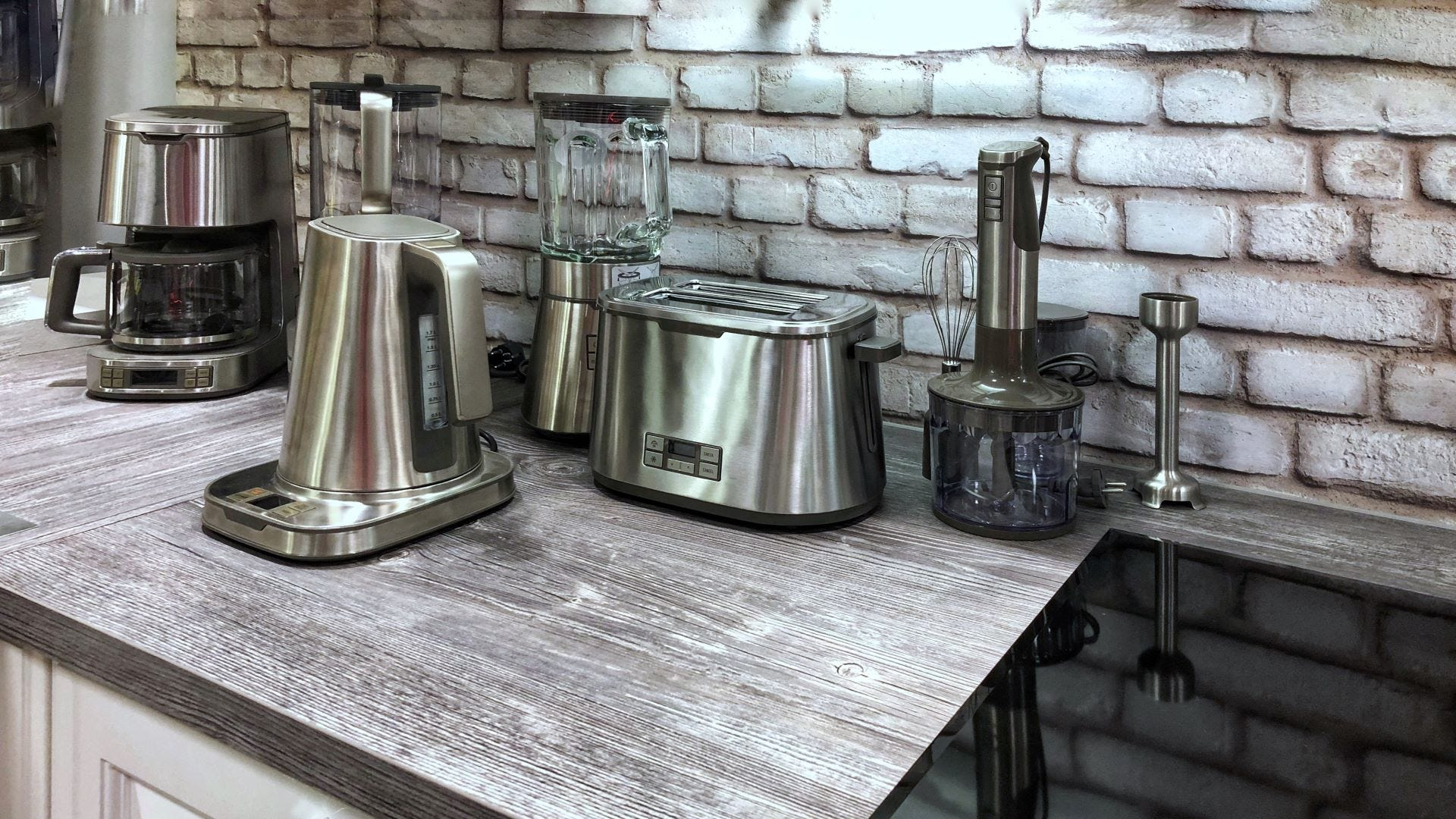 Small stainless-steel kitchen appliances sitting on a counter.