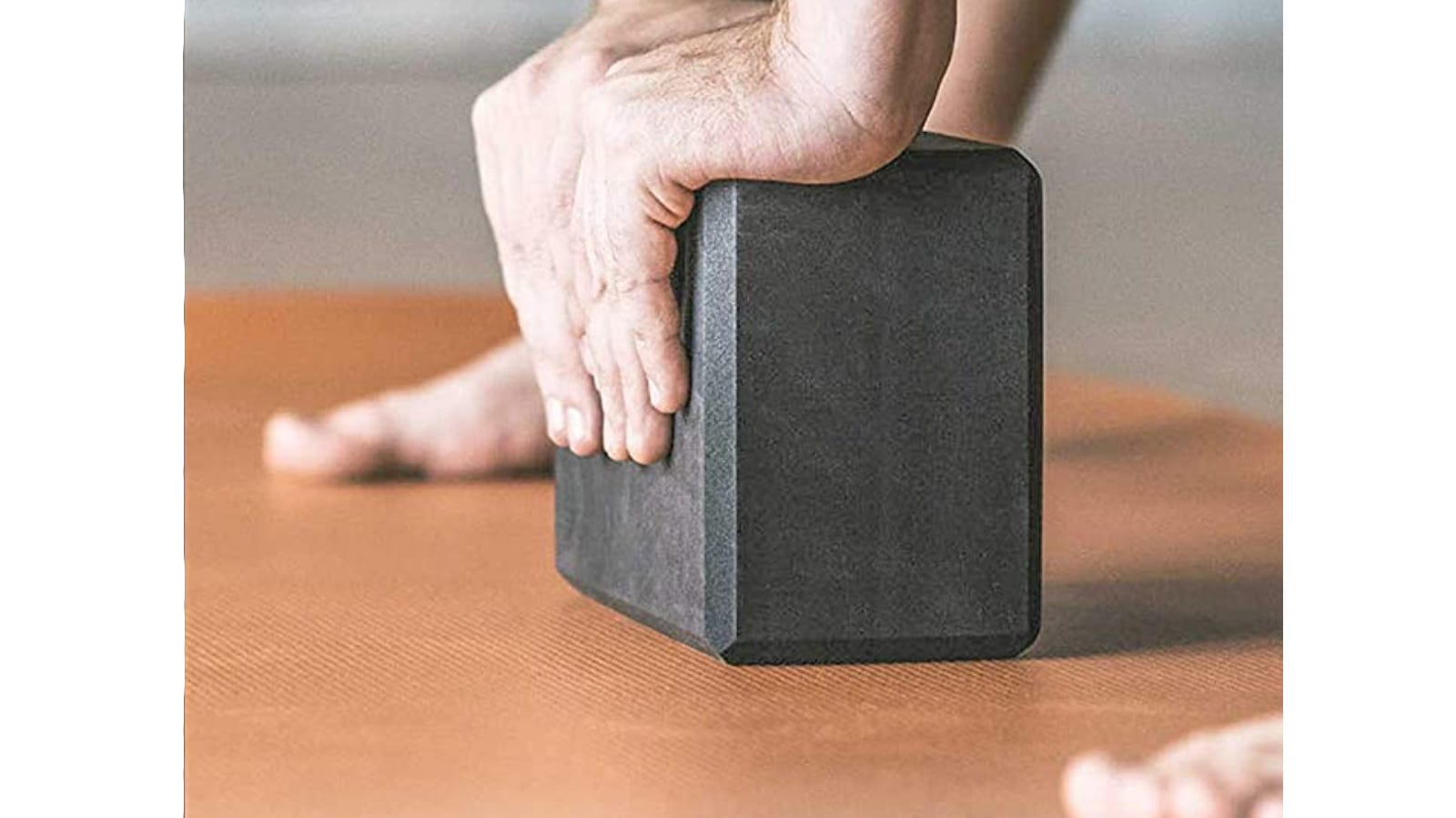 A person's hands placed on a grey yoga block with the persons feet on either side.