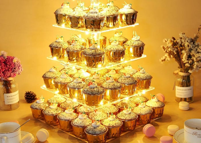 a golden light-up cupcake stand with four tiers that's full of frosted cupcakes. Macarons and flowers are in the background.