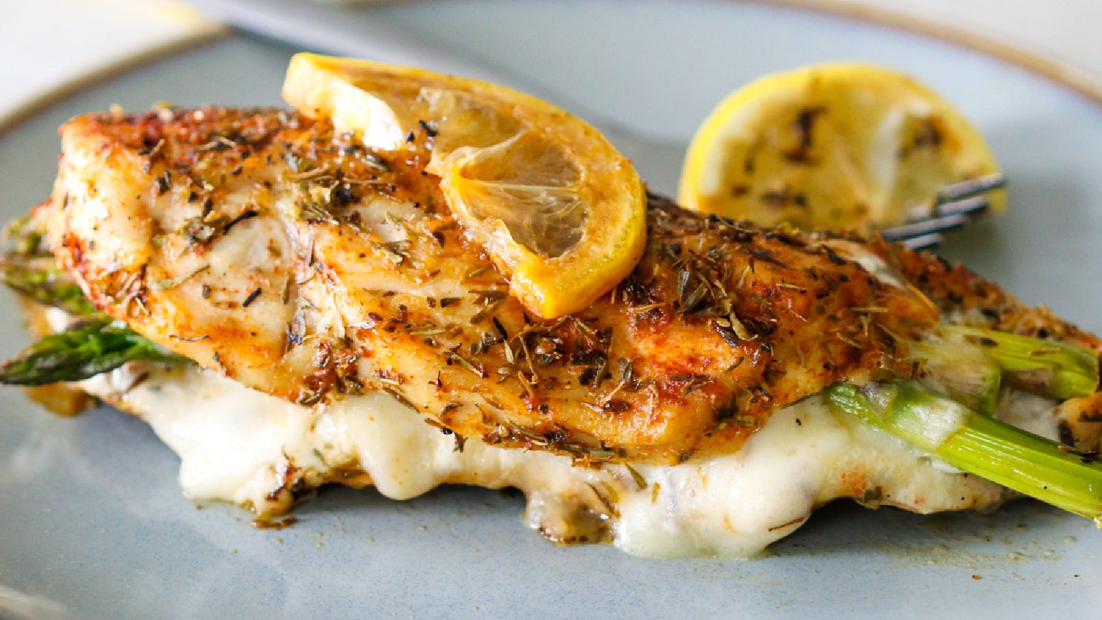 An asparagus and cheese stuffed chicken breast, coated with herbs and topped with roasted lemon slices.