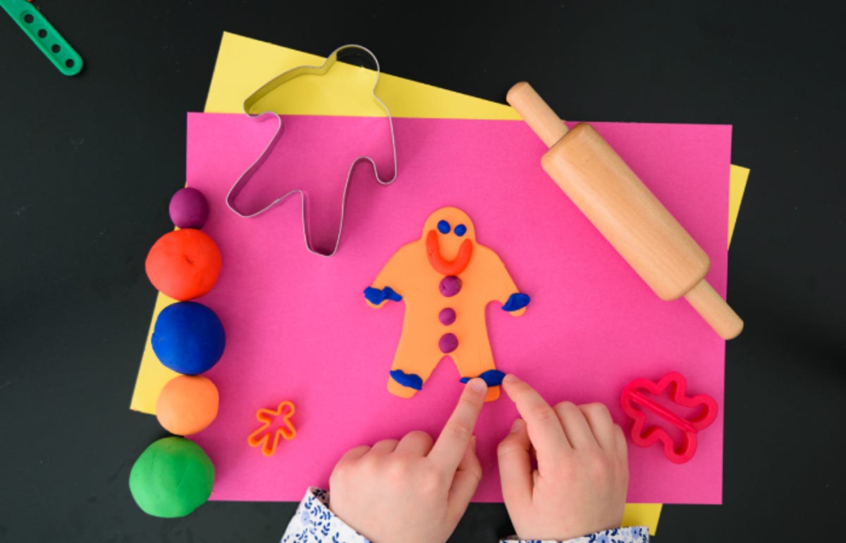 hands making a gingerbread man with play dough and tools