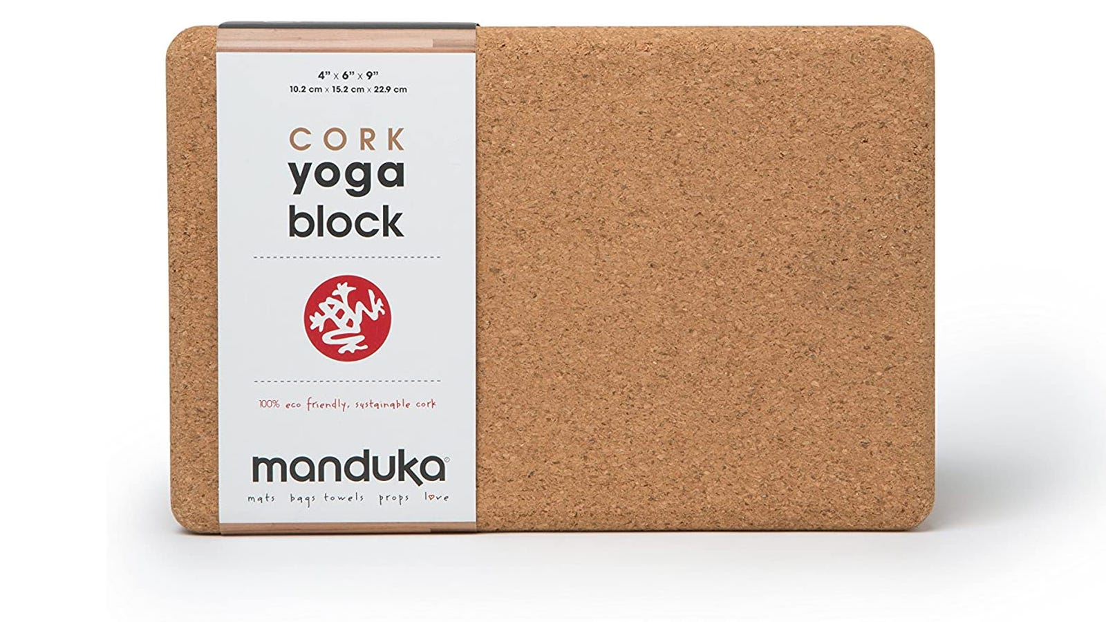 A yoga block made from cork with a label that states the brand Manduka.