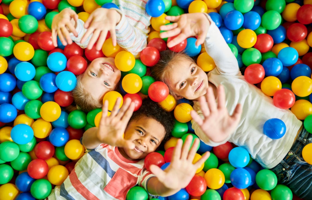 Above view portrait of three happy little kids in ball pit smiling at camera raising hands