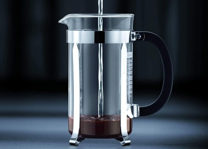 Glass French press coffee maker with minimalist stainless steel jacket and black plastic handle.