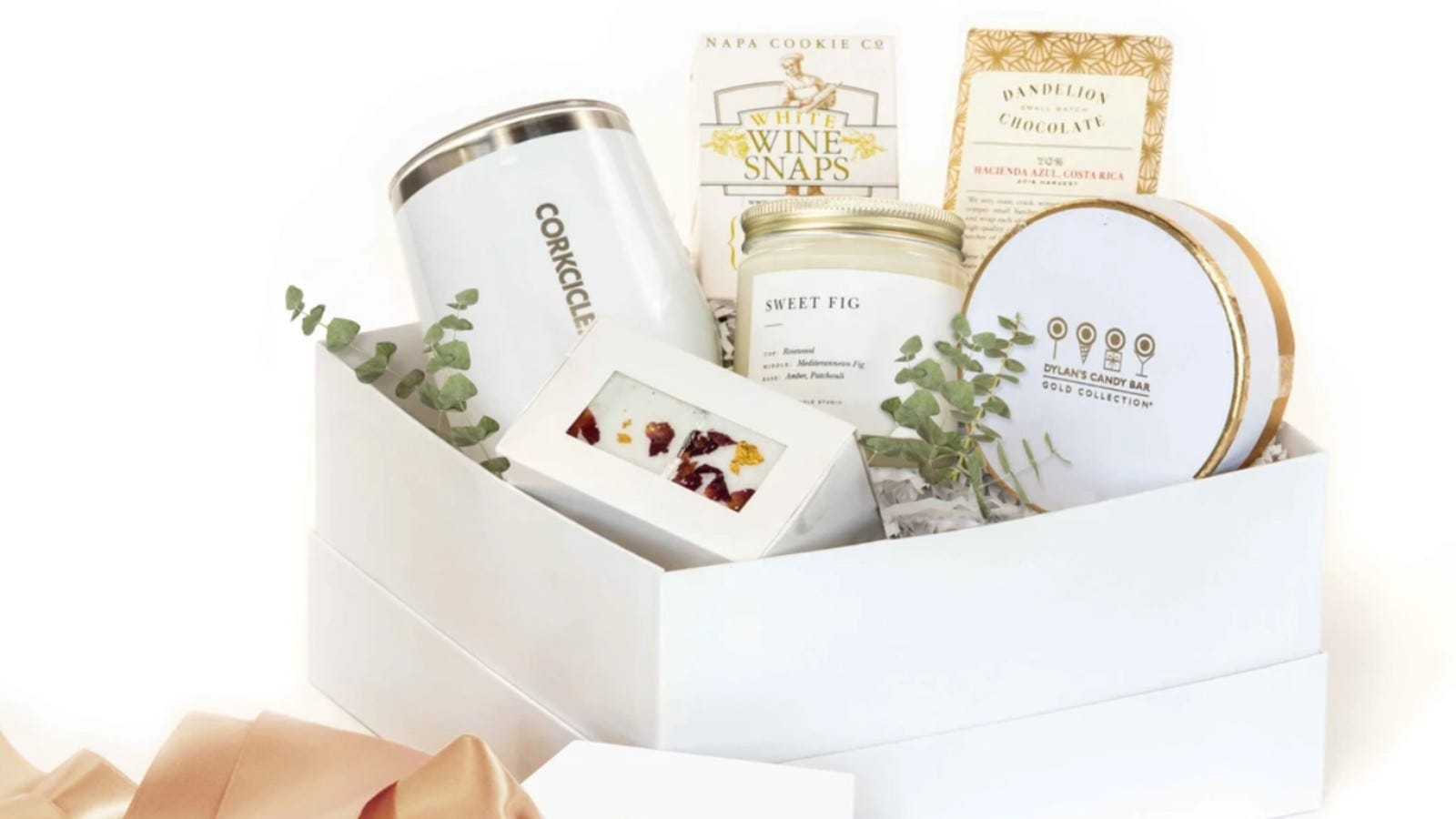 white gift box with eucalyptus sprigs for decoration, and a variety of gifts including a wine tumbler, candle, and chocolates