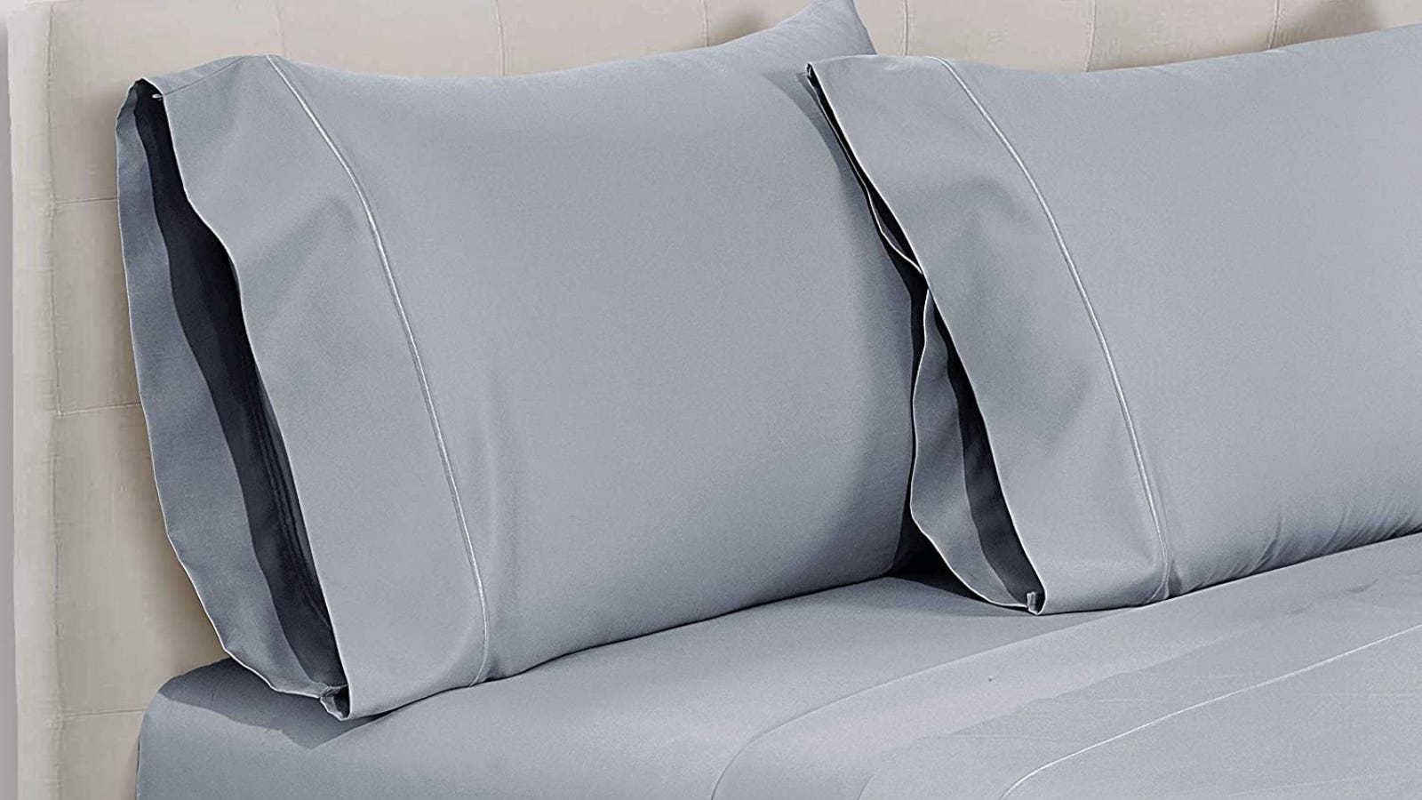 Two silver pillows and a matching sheet being displayed on a bed.