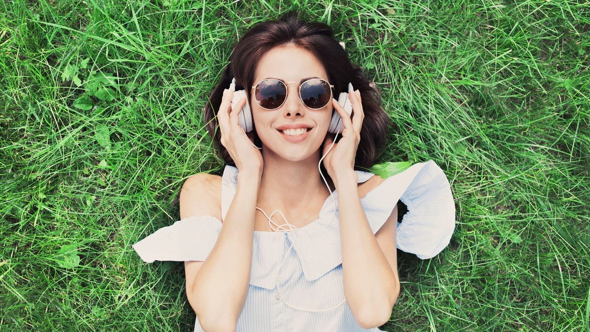 A woman lying on the grass listening to music on headphones.