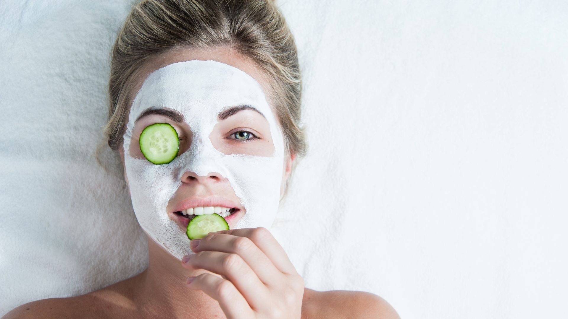 A woman eating a cucumber slice, with another resting on her eye.