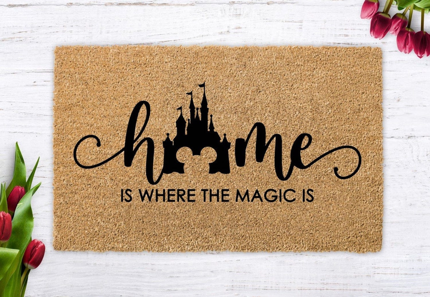 """A doormat reading """"Home Is Where the Magic Is"""" with a design of the Disney castle"""