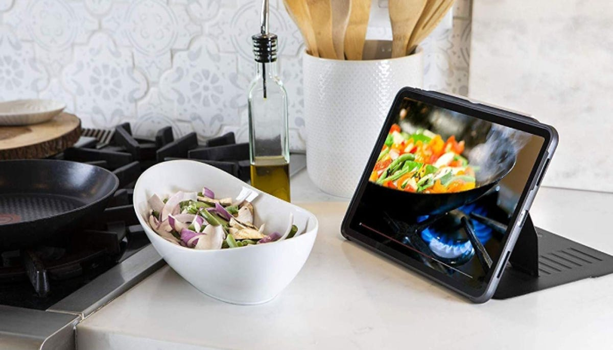 an iPad in a standing case resting on the kitchen counter next to the stove
