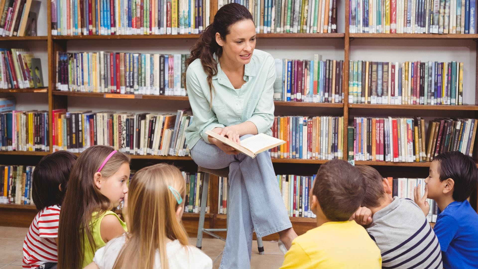 A woman reading a book to a group of kids during storytime at a library.