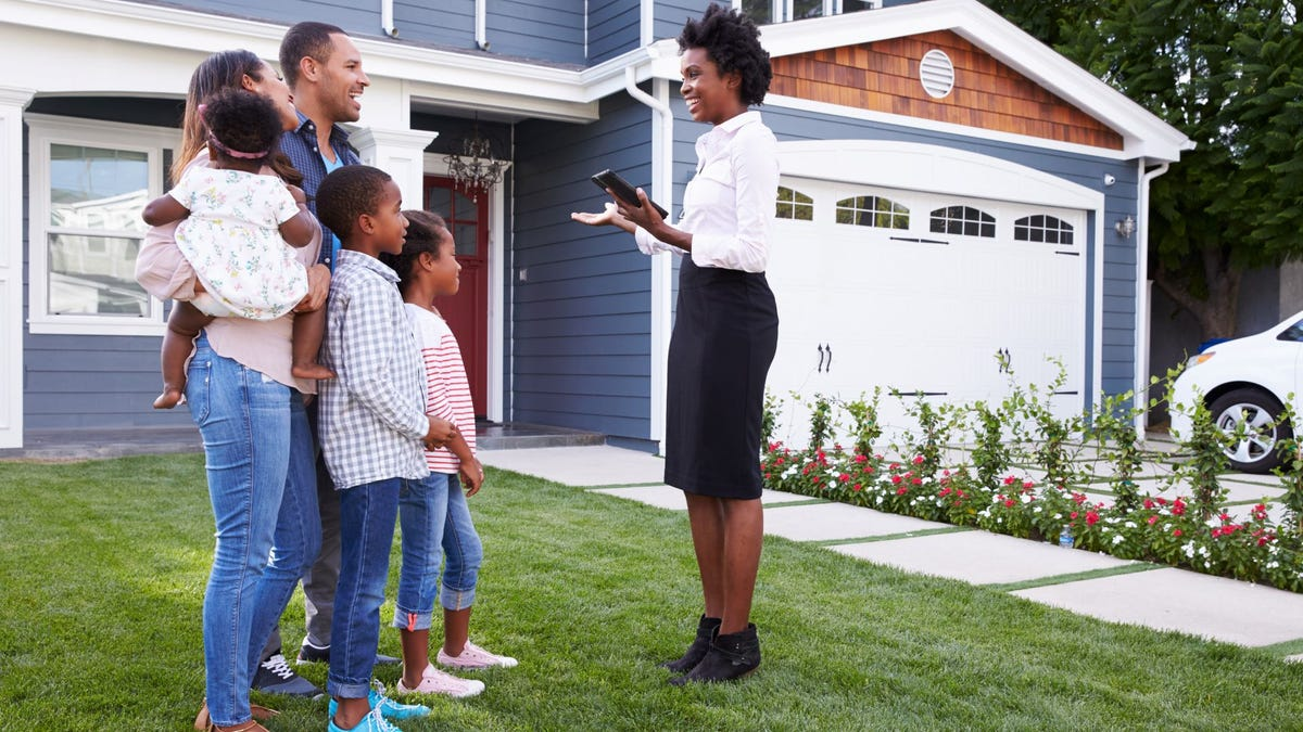 A real estate agent showing a family a house.