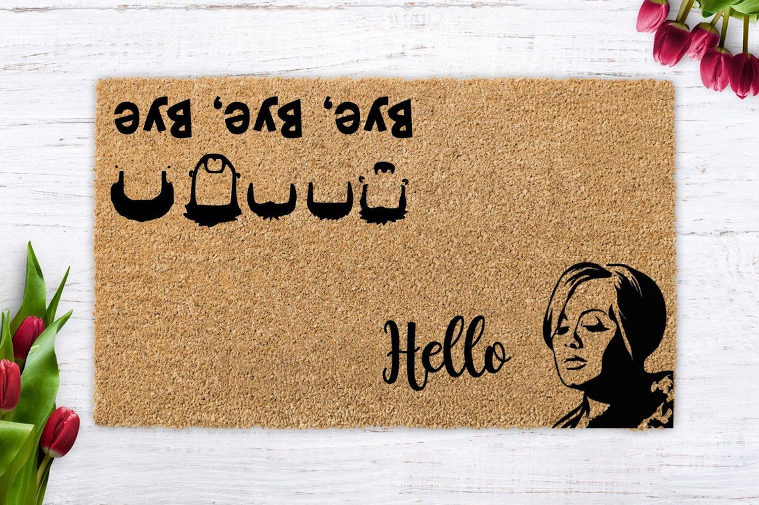 """Doormat saying """"Hello"""" with an Adele silhouette facing one way and """"Bye Bye Bye"""" with NSYNC silhouettes the other way"""