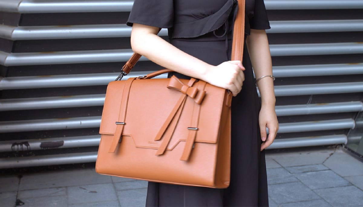 a woman in a black dress wearing a stylish brown leather messenger bag
