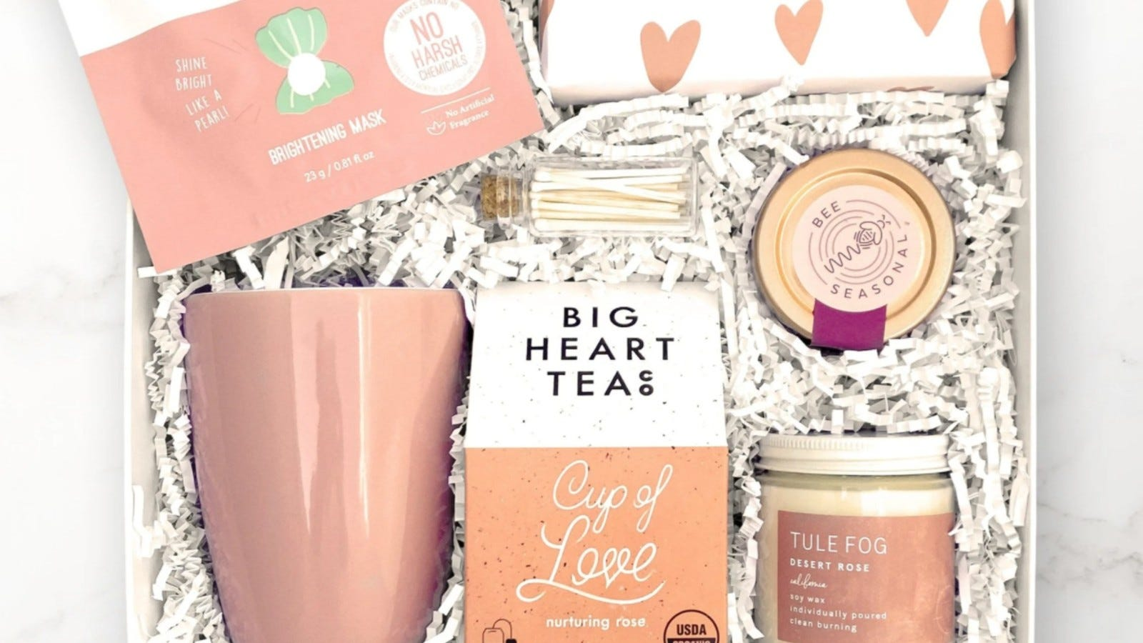 a pink and white gift box with a mug, matches, ta, candle, and honey inside