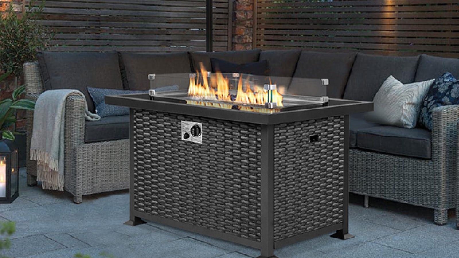 Uma linda mesa de fogo retangular da U-Max, se encaixa perfeitamente no meio da mobília de estilo sofá, em um ambiente externo aconchegante.