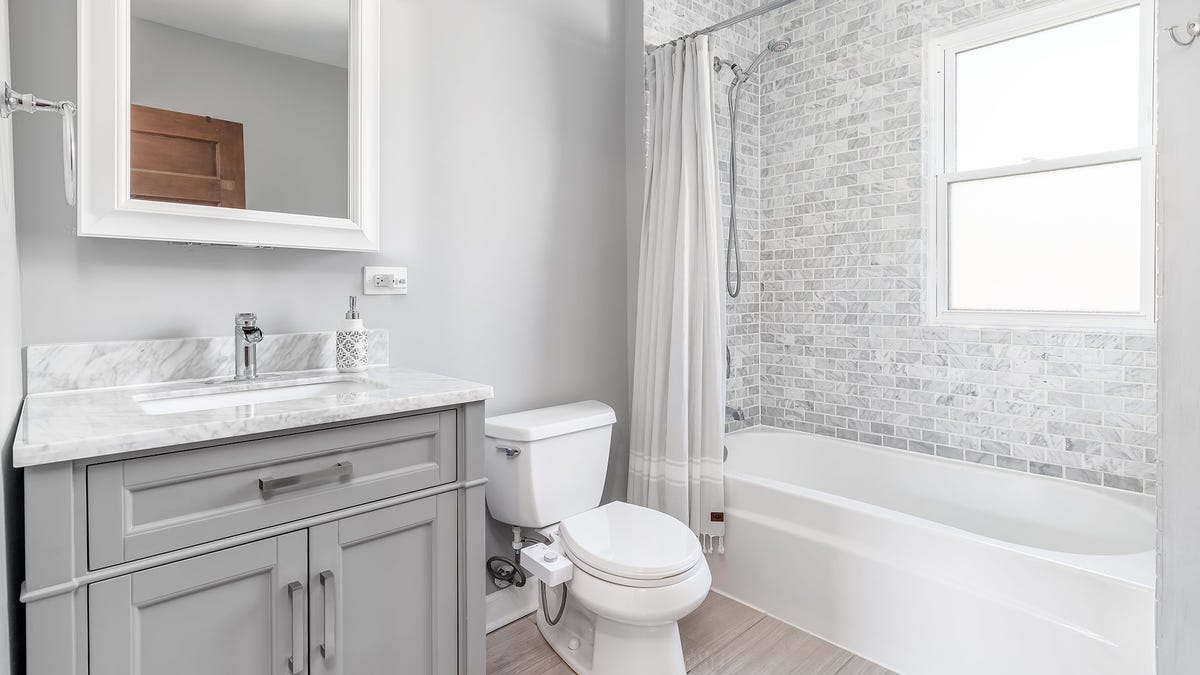 A brightly lit bathroom with a sparkling clean tub and shower.