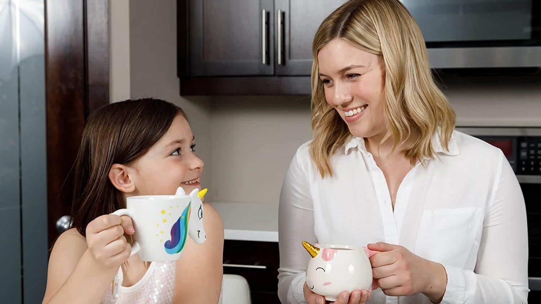 Mother and child enjoying drinks from unicorn mugs.