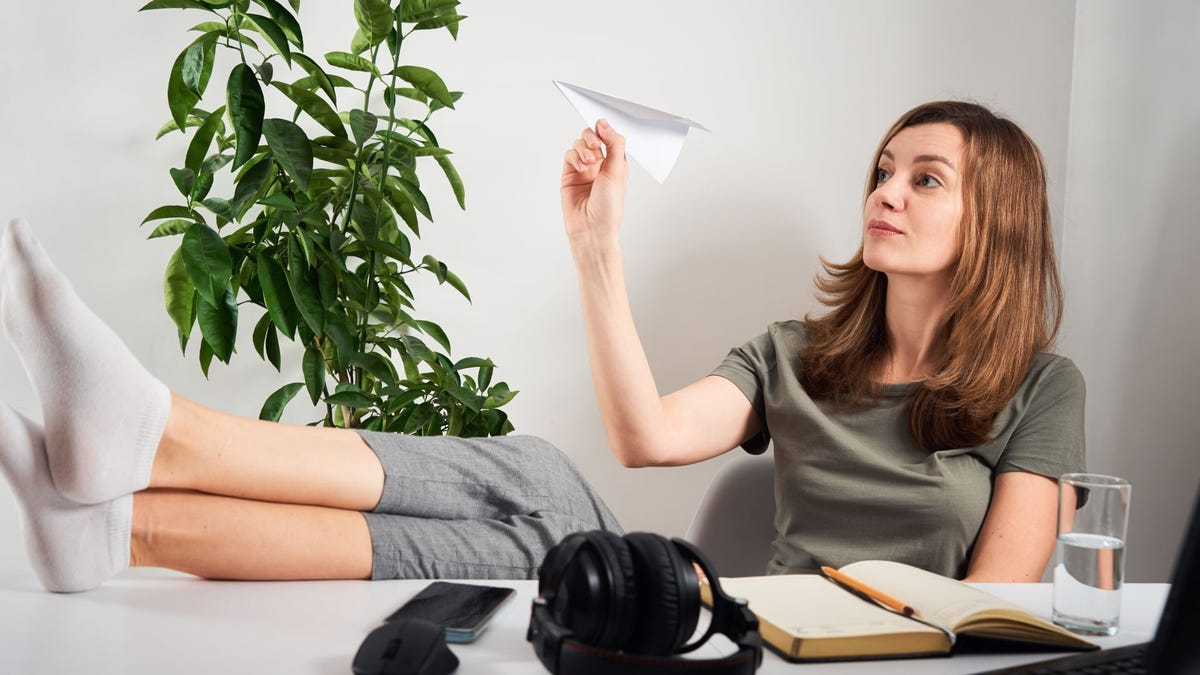 A woman sitting at a desk holding a paper airplane.