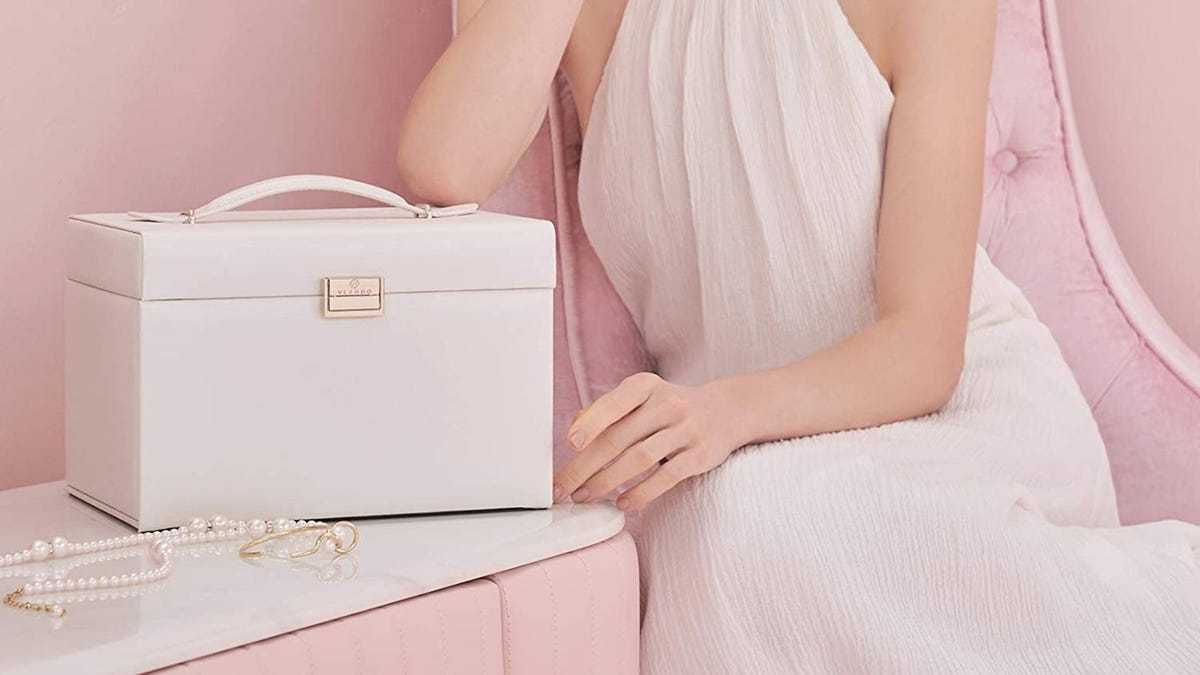 A white jewelry box is placed on a table next to pearl jewelry wile a woman wearing a white dress sits to the right.