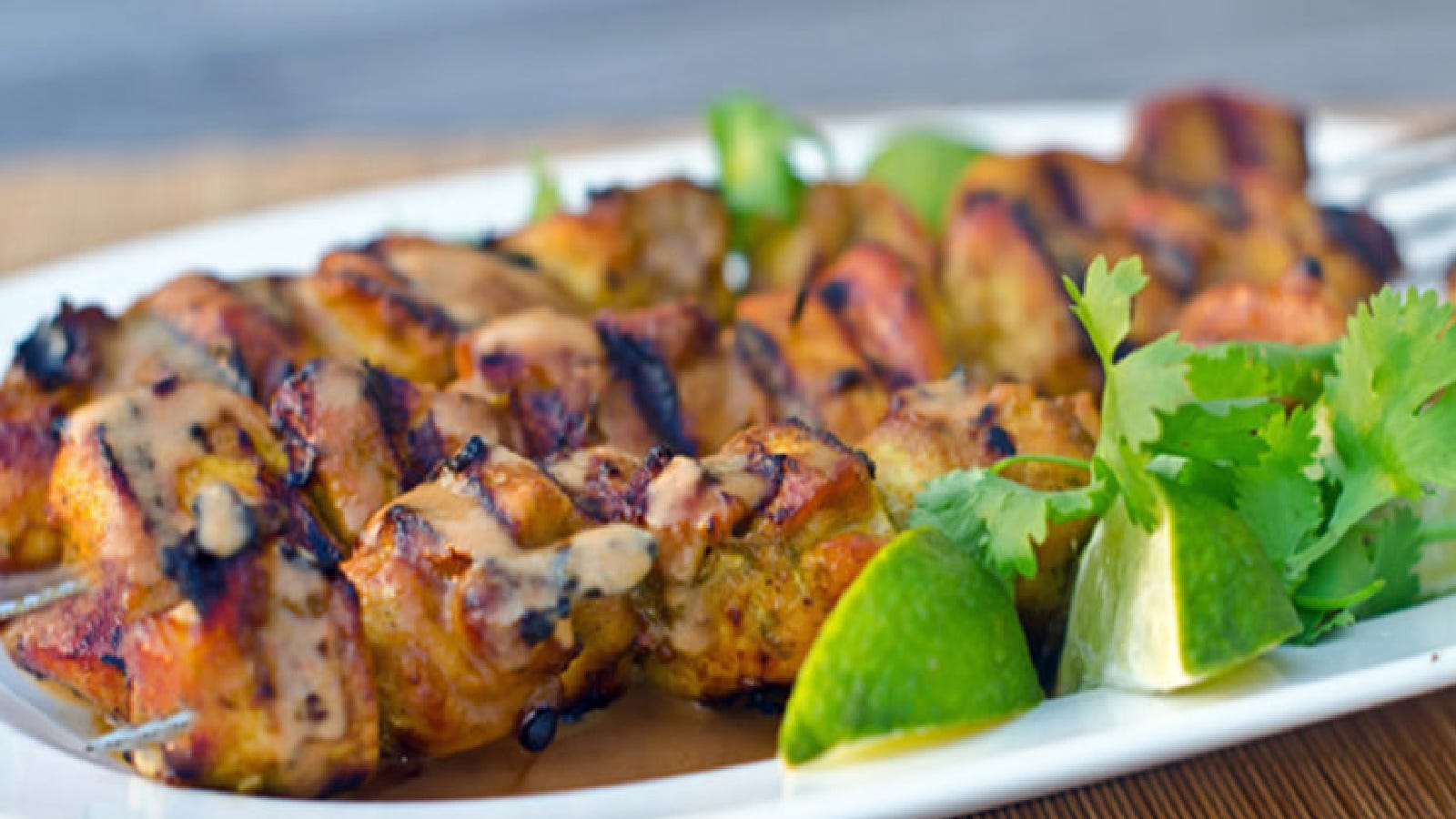 thai curry chicken skewers with a coconut peanut sauce, served with lime wedges.
