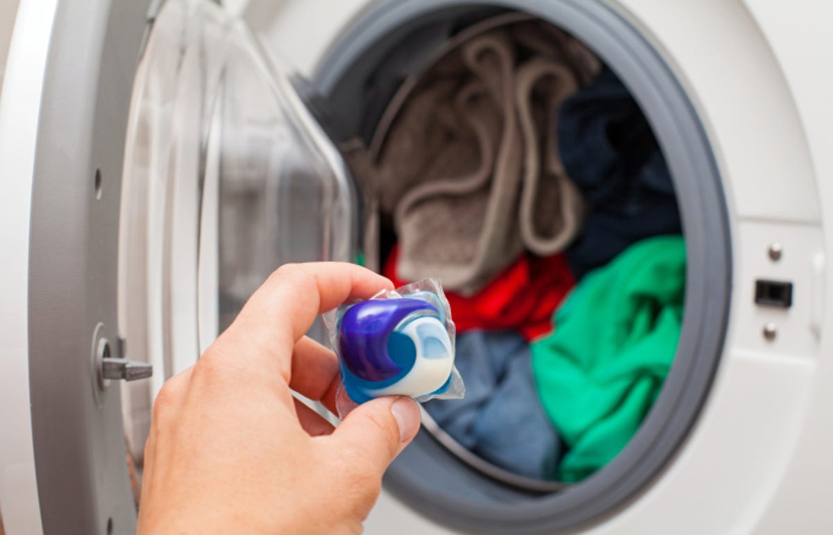 hand holding laundry detergent pod capsule, washing machine with laundry in the background