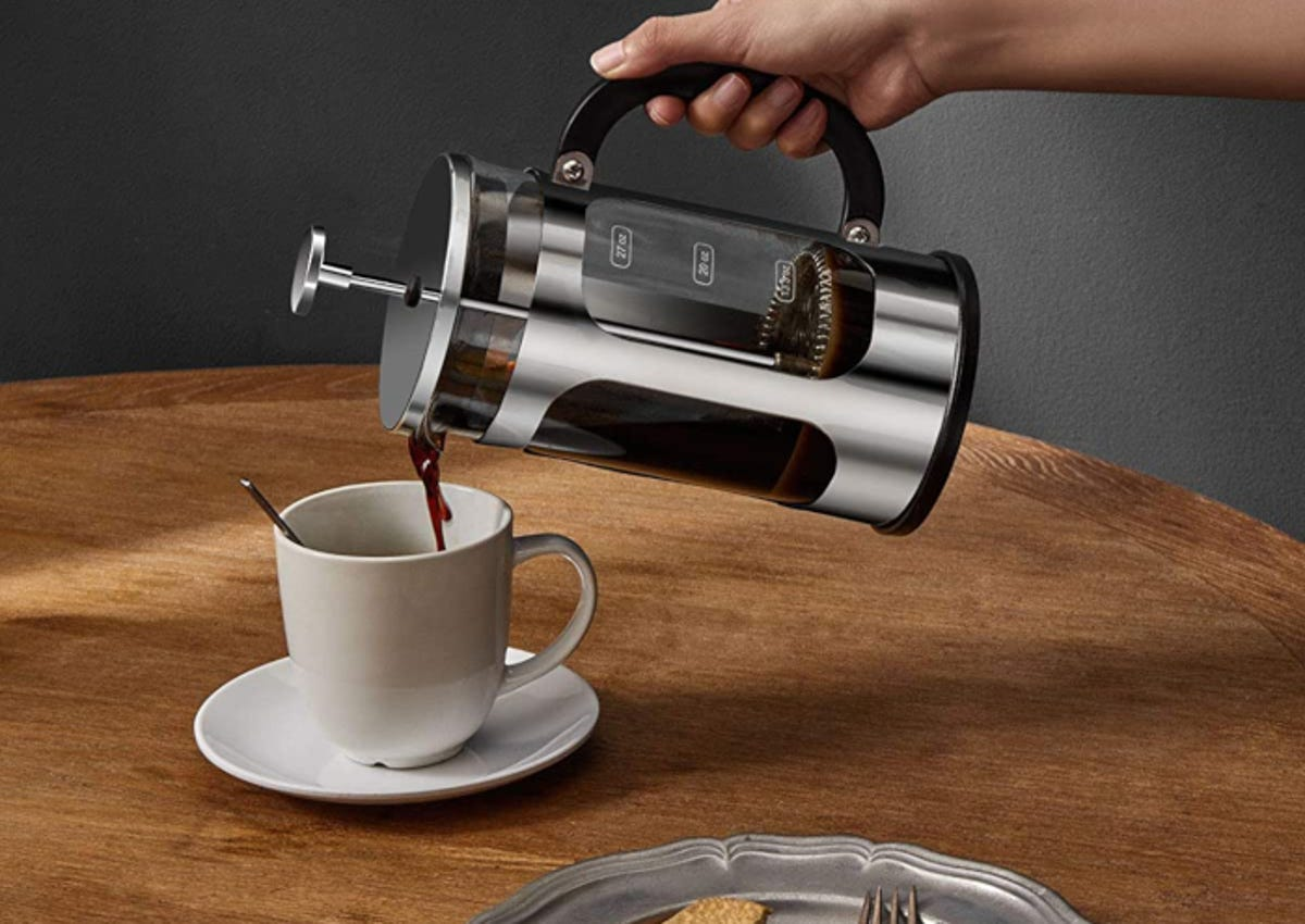 a hand pouring coffee from a stainless steel and glass French press coffee maker into a mug