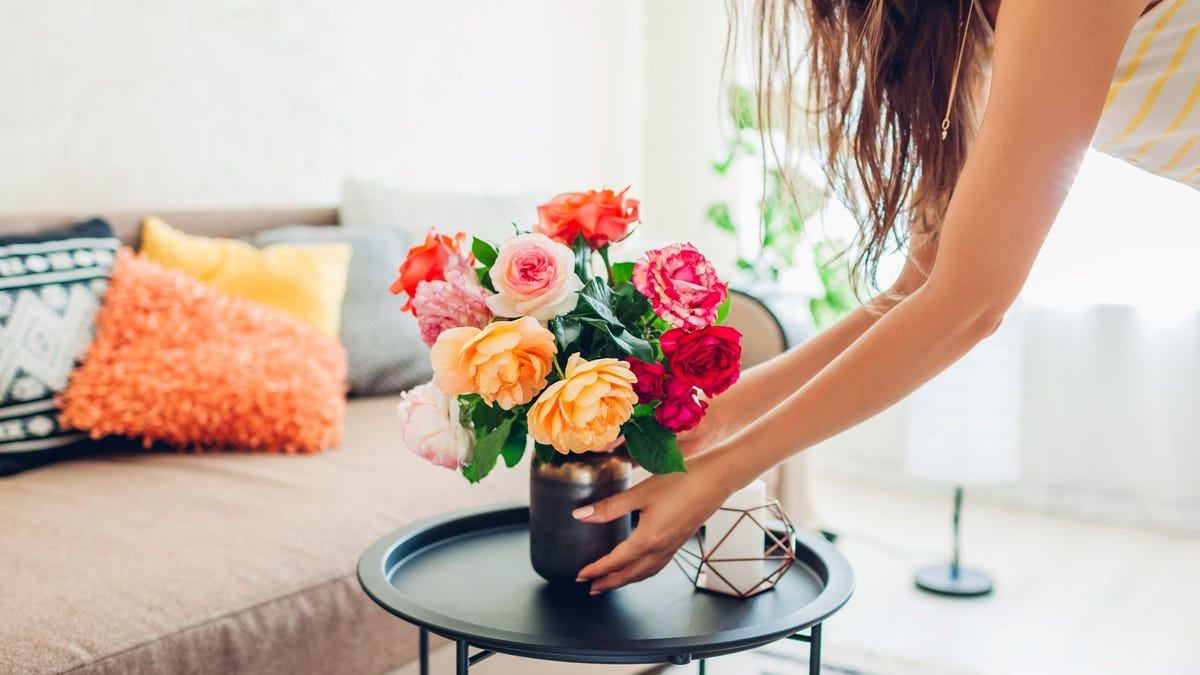 A woman placing a bouquet of flowers in a vase on a table.