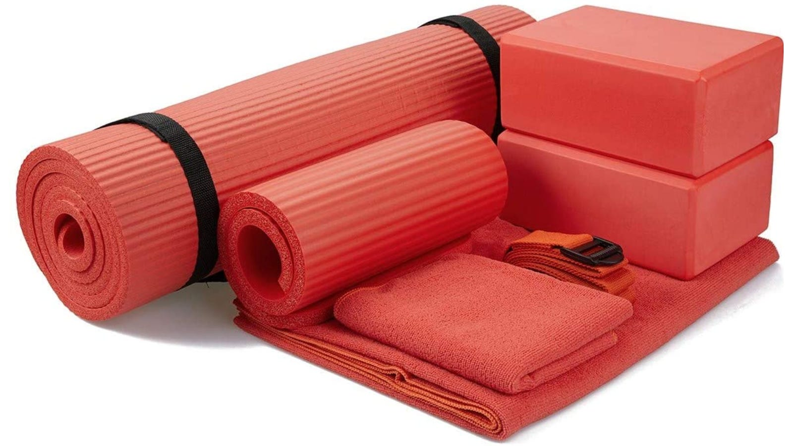 A red yoga set that has a rolled up yoga mat, carrying strap, small knee mat, two yoga blocks, a stretch strap, and two towels.
