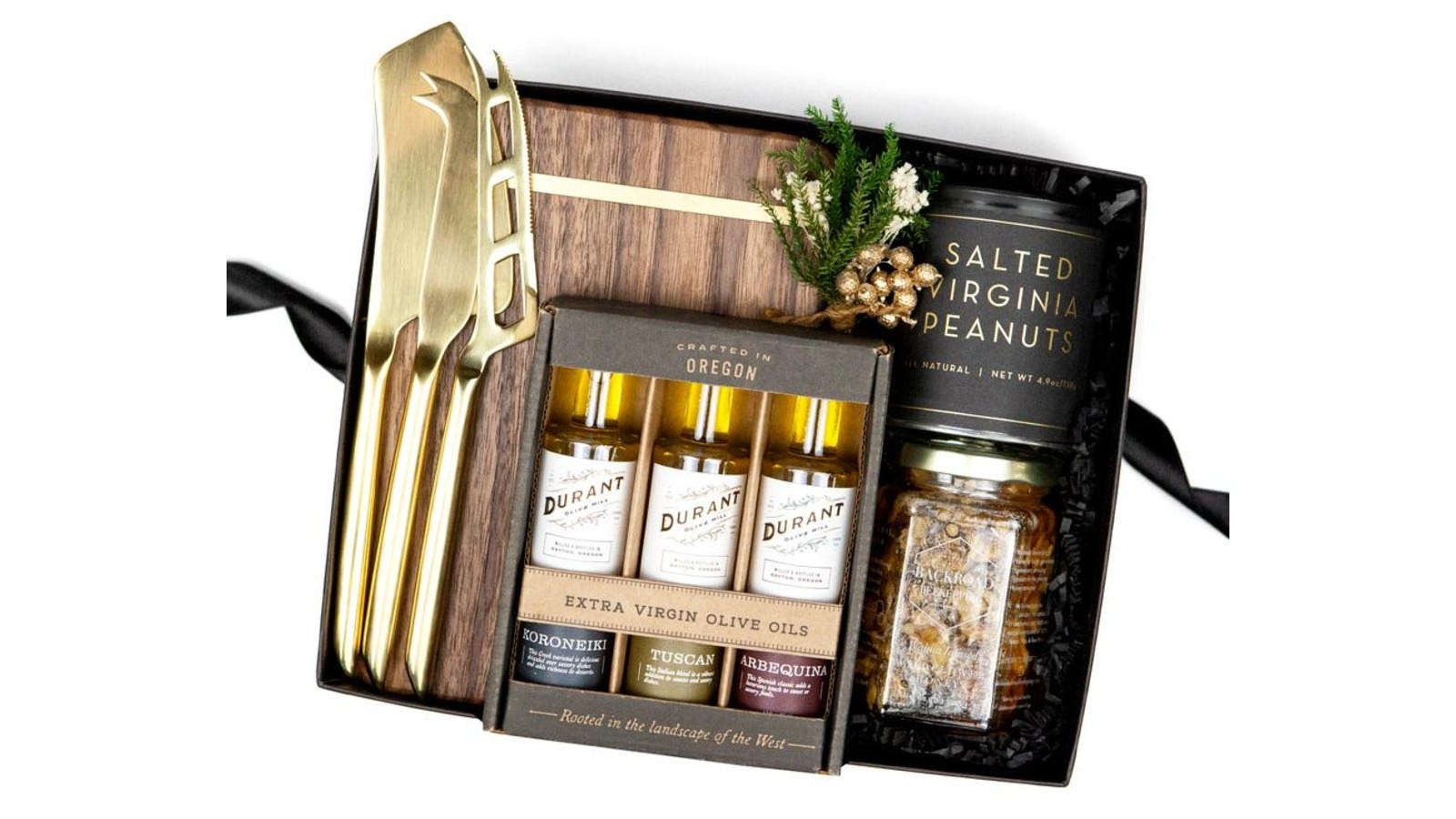 a dark gift box with a wooden cheese board, gold cheese knives, an olive oil set, peanuts, and honey