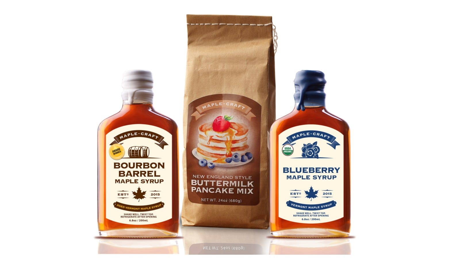 two bottles of maple syrup with a bag of pancake mix in the center