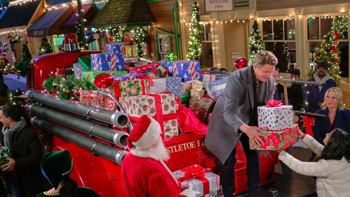 A man hands present out off the back of a red fire truck with the help of Santa Claus.