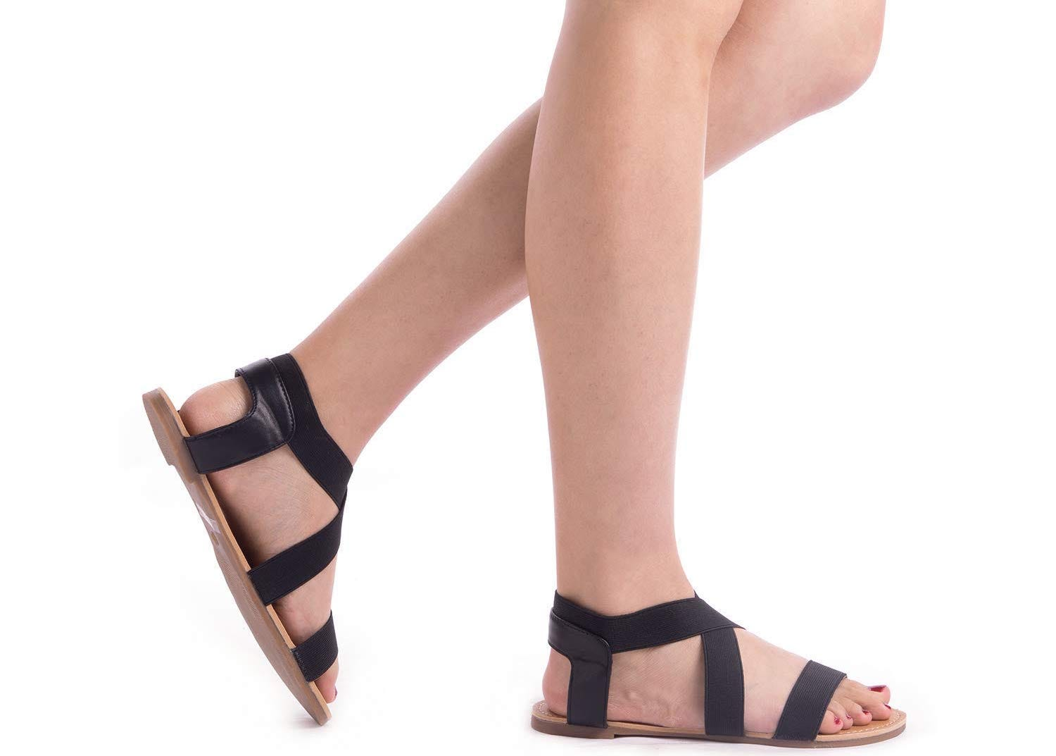 A pair of women's legs wearing black strappy sandals