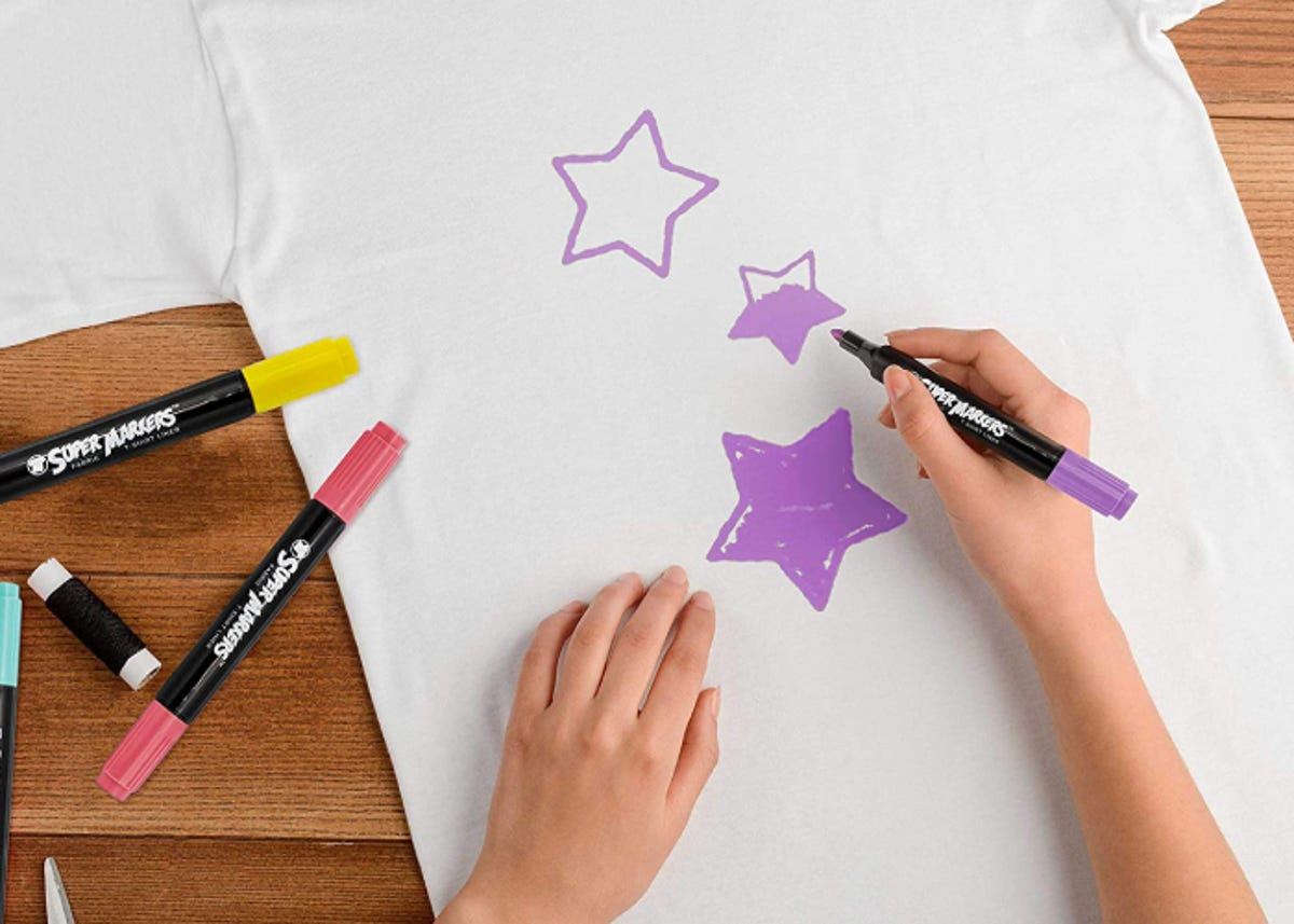 hand drawing stars on white t-shirt with a purple fabric marker. Other colored markers are close by.