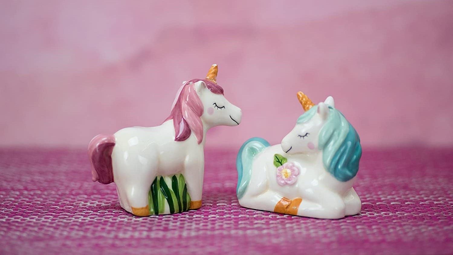 Unicorn salt and pepper shakers sitting on a table.