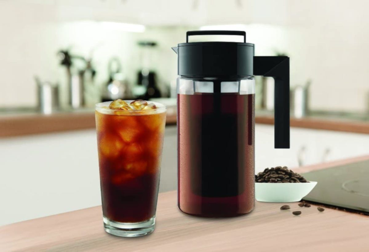 Cold brew coffee maker filled with cold brew concentrate next to a glass of iced cold brew coffee
