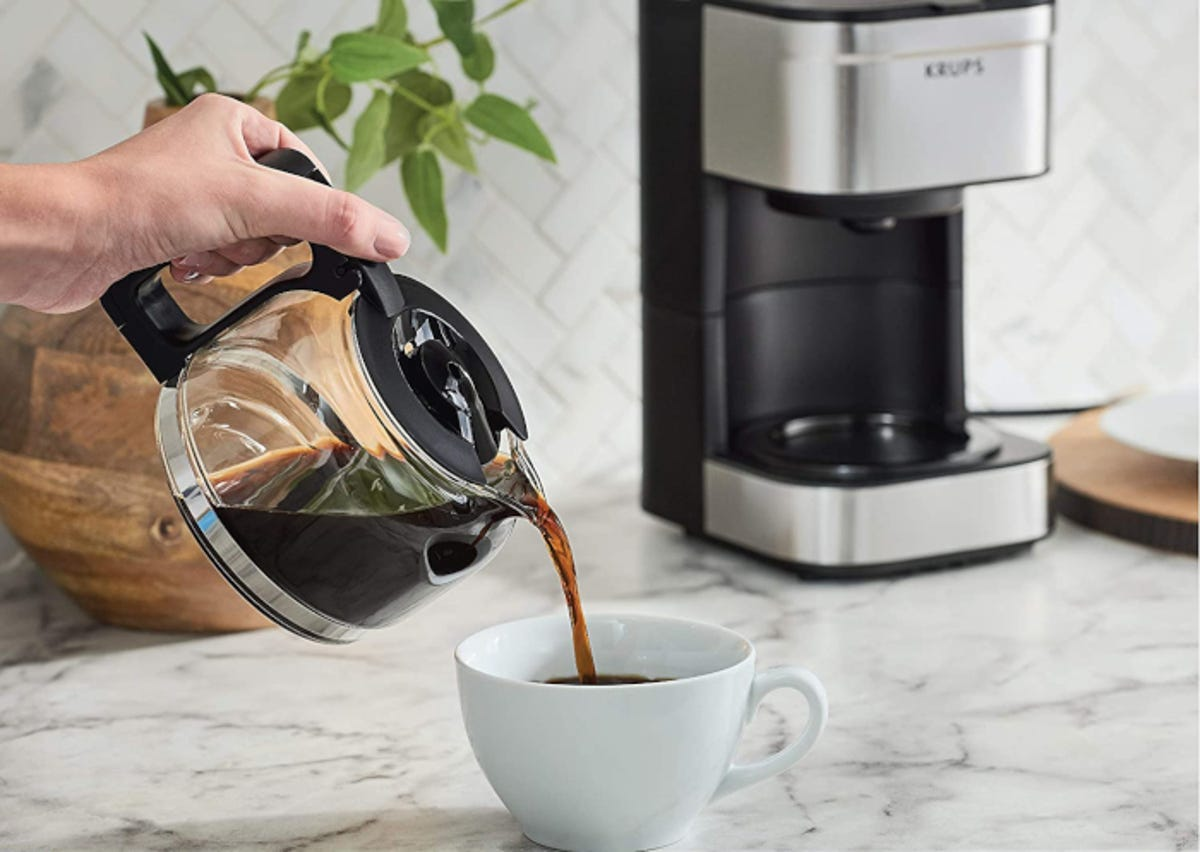 Hand pouring coffee into a mug with stainless steel drip coffee maker in the background