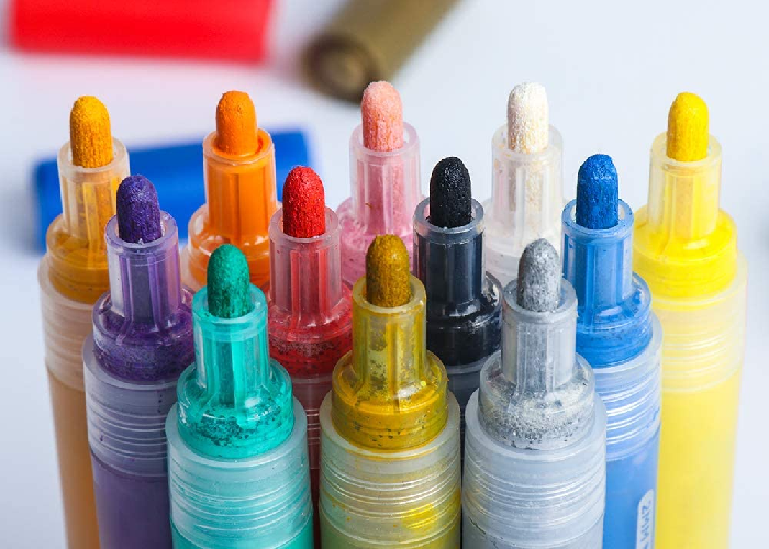 Twelve fabric paint markers with their caps off showing the tips of the pen.