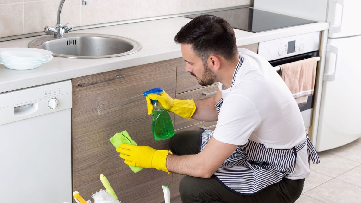 A man cleaning the drawers in a kitchen.
