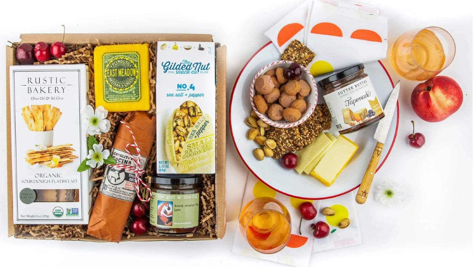 a box of assorted packaged snacks next to a snack plate of cheese and nuts