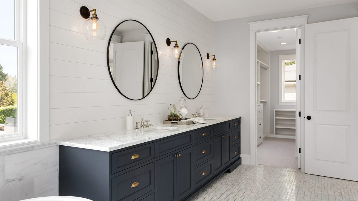 A large modern bathroom with a clean and clutter free dual-vanity sink.