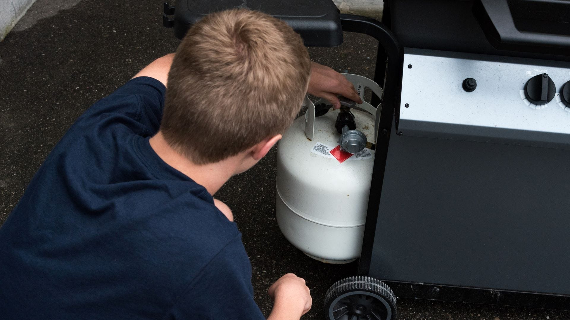 A young boy checking the propane tank on a grill.