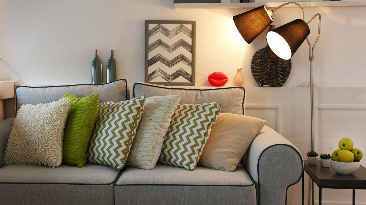 A modern living room with a gray couch lit by a floor lamp.