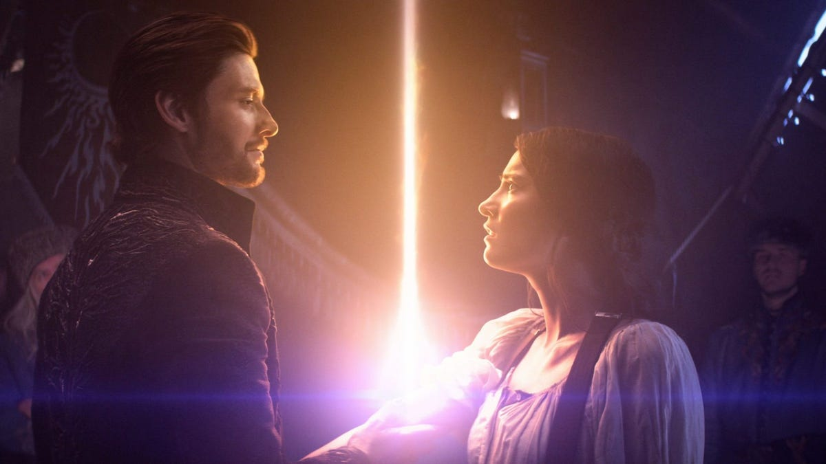 A man holds a woman arm and sunlight beams up from where his hand is placed.