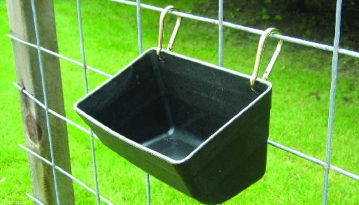 A black hanging horse feeder is shown attached to a square wire fence against a backdrop of bright green grass.