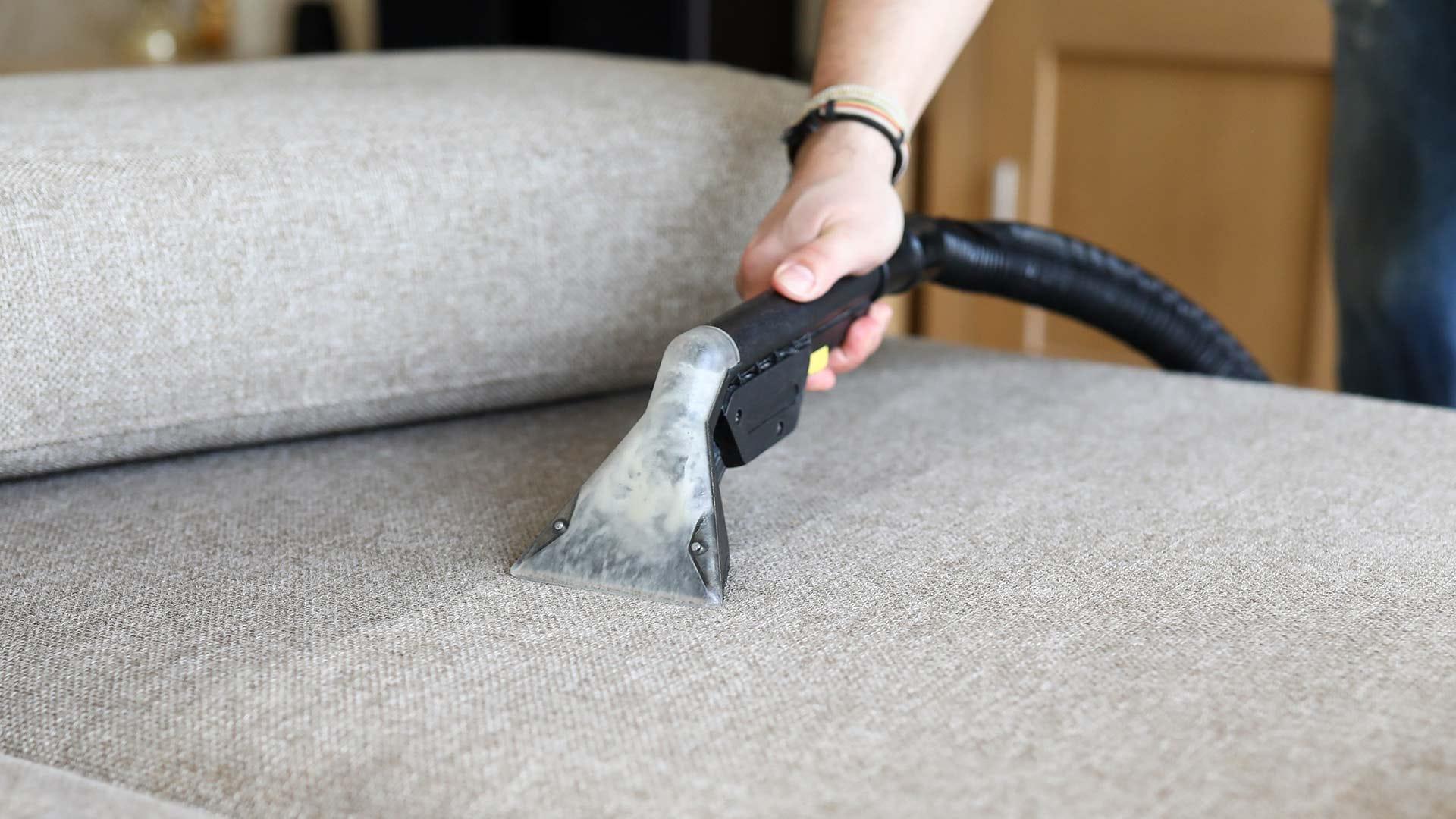 Une personne utilisant une machine de nettoyage de tissus d'ameublement sur son canapé.