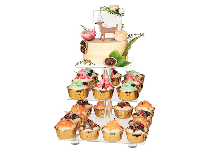 clear, acrylic, cupcake stand with three square-shaped tiers displaying brown, orange, and green cupcakes on the two bottom tiers with a small round cake on the top