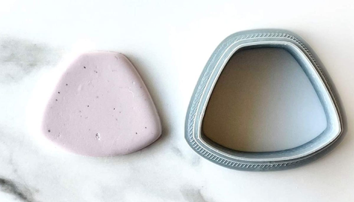 polymer clay cutter in a curved trapezoidal shape with cut out clay next to it on a marble surface