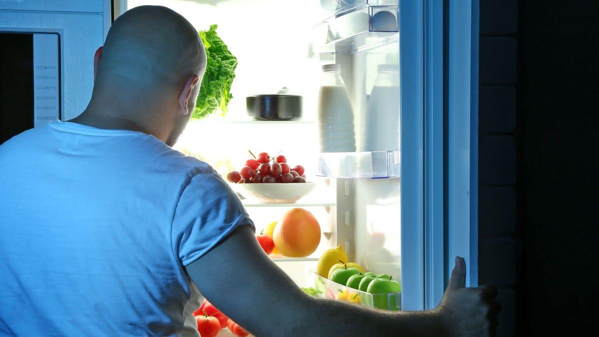 Man peering into a fridge at food.