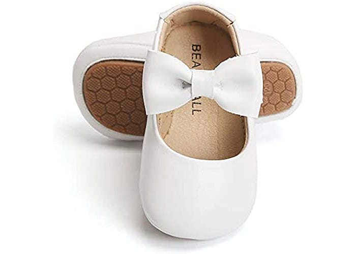 white baby girl dress shoes with a big bow over the top of the foot